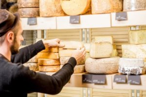 person stacking cheese wheels